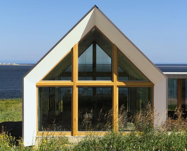 Ici, une structure d'acier renforce la fenestration en chêne blanc. «Elle n'est pas porteuse, mais tel un cadre, elle évite que le bâtiment ne fléchisse. C'est un contreventement», détaille Loukas Yiacouvakis. L'ensemble des fenêtres est doté d'un triple vitrage, «en raison de sa valeur isolante supérieure», ajoute-t-il. Une fine bordure de tôle d'acier souligne la forme du pignon. Observez aussi la transparence de l'espace de vie. (PHOTO PASCAL ANNAND, FOURNIE PAR YH2)