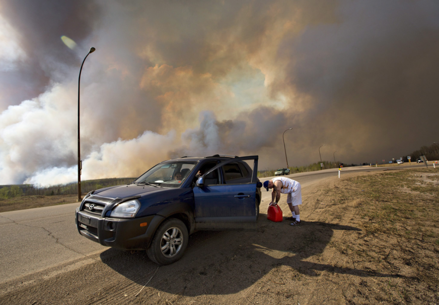 Un résidant de Fort McMurray met de l'essence... (PHOTO JASON FRANSON, LA PRESSE CANADIENNE)