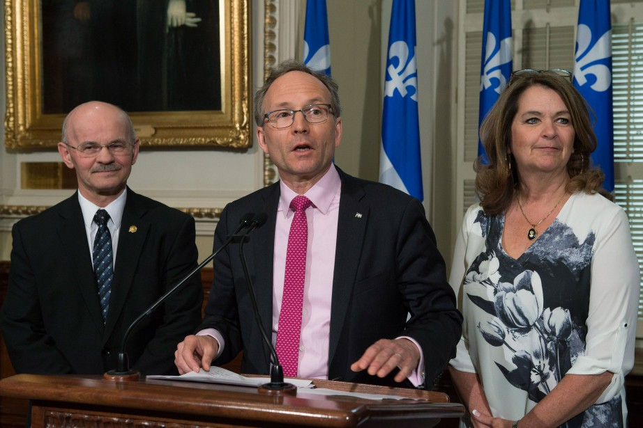 Le ministre des Affaires municipales Martin Coiteux, entouré...