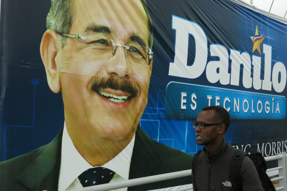 Un homme passe devant une banderole du président... (PHOTO EZEQUIEL LOPEZ, ARCHIVES AP)