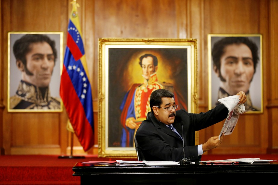 Le président Nicolas Maduro regarde un journal alors... (PHOTO CARLOS GARCIA RAWLINS, REUTERS)