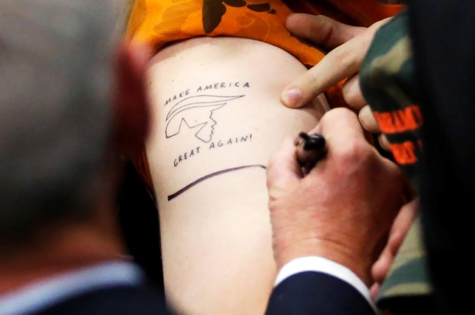 Un partisan de Trump fait signer son tatouage... (Photo Reuters)