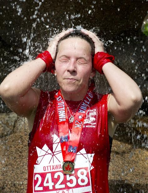 Kati Kaubfsh se rafraîchit à la fontaine du parc de la Confédération après sa course de 5 km. (Martin Roy, LeDroit)