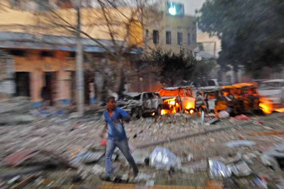 Un homme court quelques instants après qu'une voiture... (PHOTO MOHAMED ABDIWAHAB, AFP)