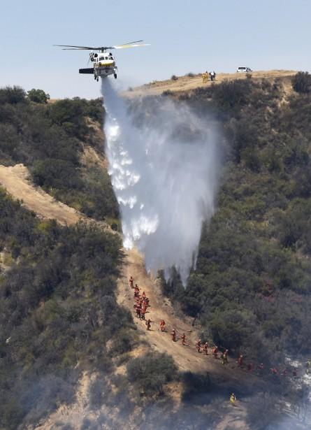 Un hélicoptère largue de l'eau sur le feu de bois et de broussailles, à Calabasas. (AFP, Michael Owen Baker)