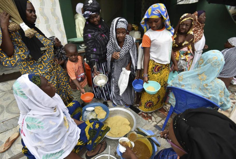 À Abidjan, des femmes distribuent des vivres devant une mosquée. (AFP)
