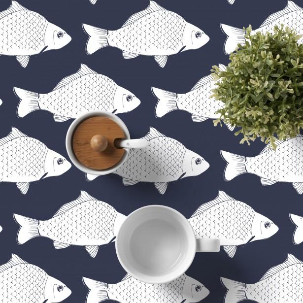 La boutique River Oak Studio présente une nappe de toile sur laquelle sont imprimés des poissons (103,19$, les frais de livraison sont en sus). ()