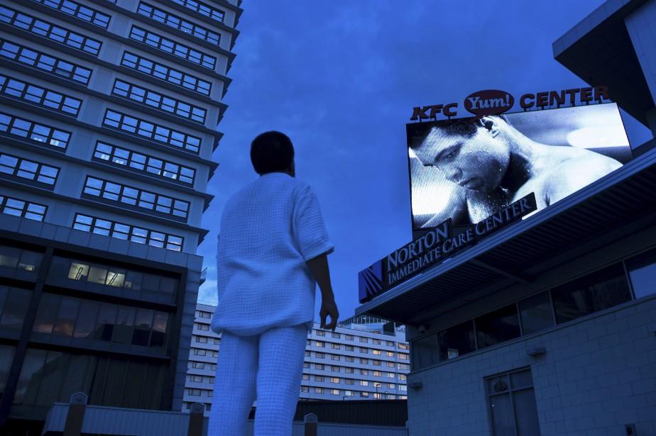Un homme regarde une photo d'Ali sur un écran à l'extérieur du KFC Center. (AFP)