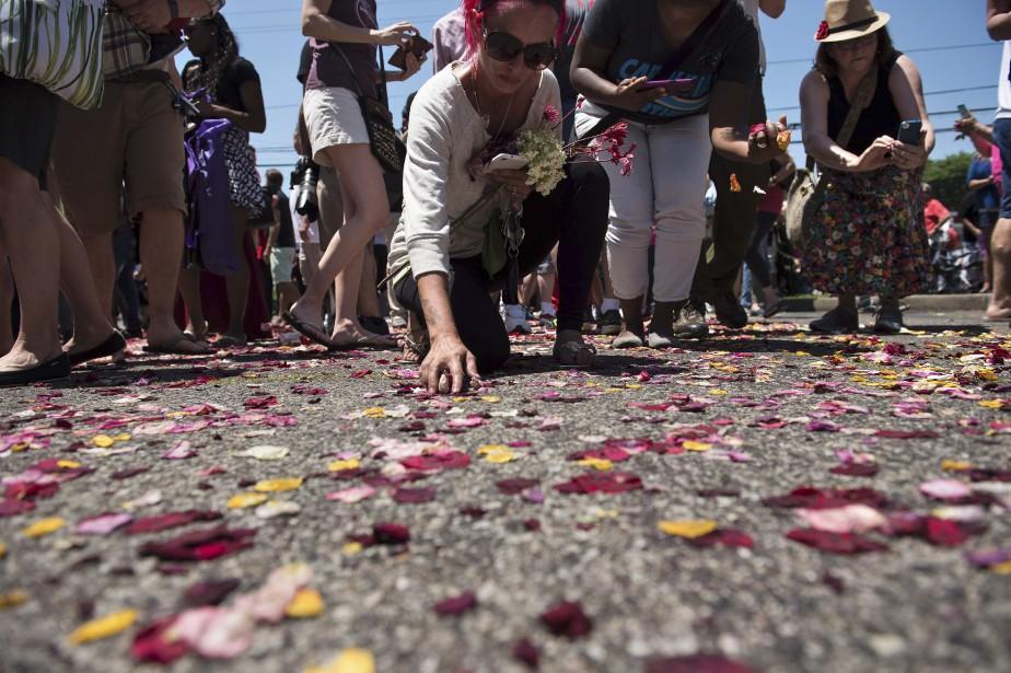 Des gens ramassent les fleurs sur le sol après le passage de la parade. (AFP)