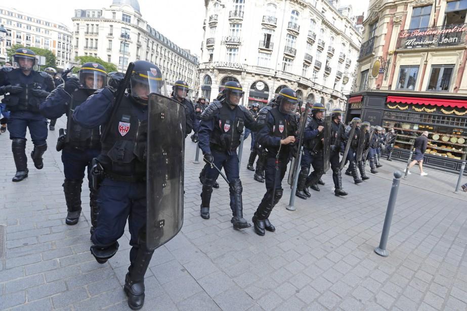 Des policiers antiémeute patrouillent dans le centre-ville de... (PHOTO Darko Bandic, AP)