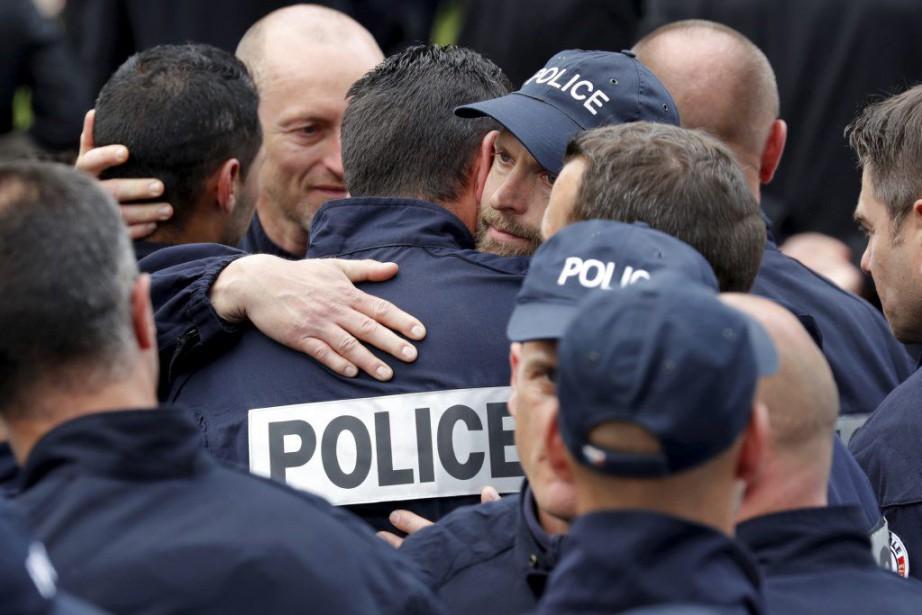 Des policiers s'étreignent lors d'une cérémonie d'hommage officiel... (PHOTO PHILIPPE WOJAZER, REUTERS)