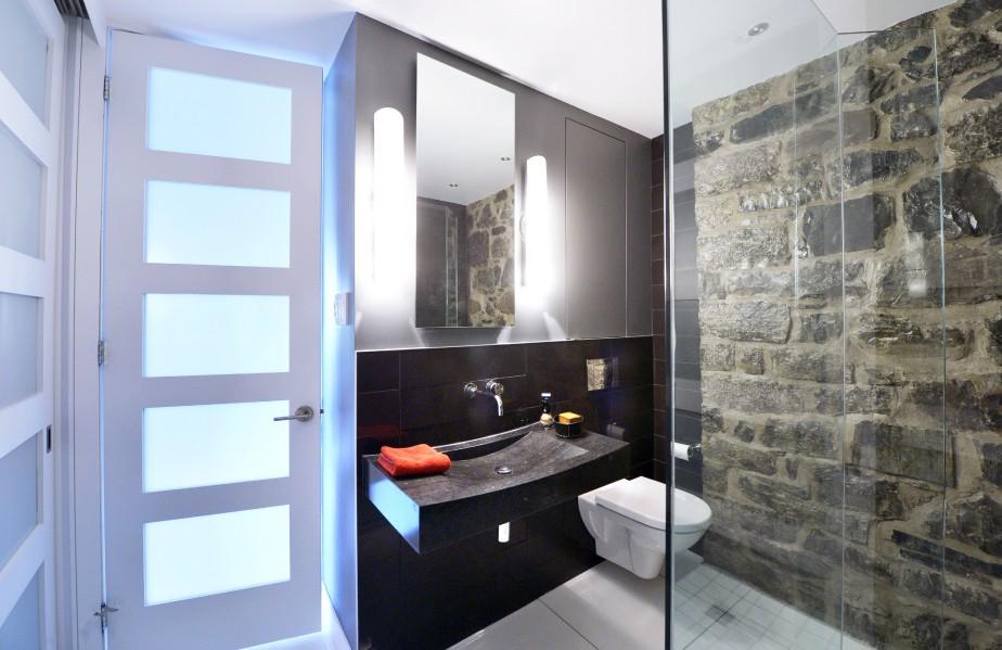 Dans la salle d'eau, un mur de pierre restauré, une douche à l'italienne et un meuble lavabo signé Le Moine Urbain, de Montréal. (Le Soleil, Jean-Marie Villeneuve)