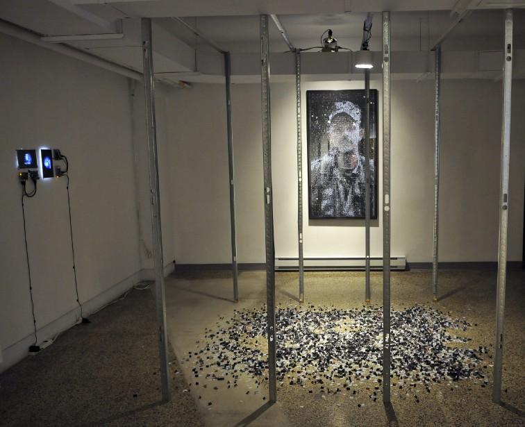 Paolo Almario propose une oeuvre lourde de sens. Le père de l'artiste est emprisonné injustement en Colombie depuis des années. Les poteaux installés rappellent justement la prison où il est enfermé. Le portrait intitulé <em>Oscar</em>, est composé de photos. Le portrait a été déconstruit dans le cadre d'une installation présentée à l'UQAC en 2014. Il a été reconstruit, mais des photos ont été perdues dans le processus. Ce sont ces «cicatrices de l'oeuvre» qui se retrouvent sur le sol. (Photo Le Progrès-dimanche, Rocket Lavoie)