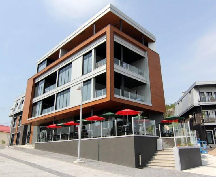 Le restaurant Au Pavillon Noir se distingue par sa bâtisse arborant une architecture moderne et sa magnifique terrasse offrant une vue imprennable sur le quai d'escale et la baie des Ha! Ha! (Facebook Au Pavillon Noir)