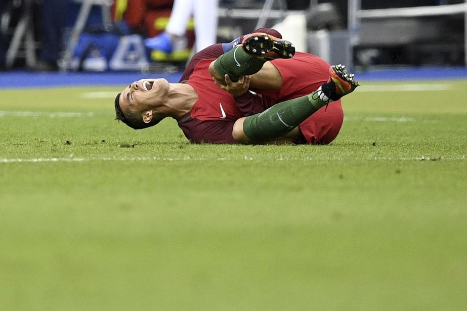 Christiano Ronaldo s'écroule au sol après une blessure au genou. Le joueur vedette sera entraîné à l'extérieur du terrain sur une civière. (AFP)