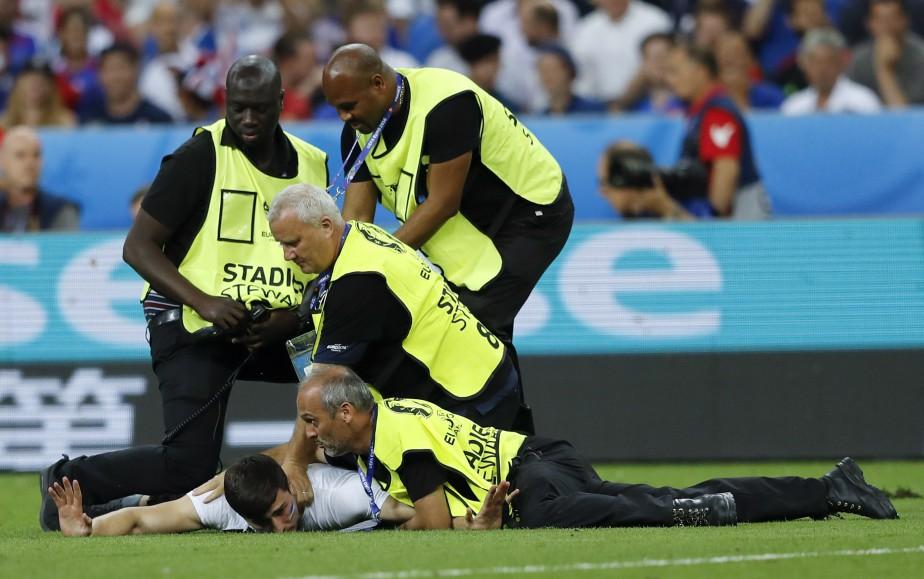 La sécurité arrête un homme qui s'est faufilé sur le terrain du Stade de France. (AP)