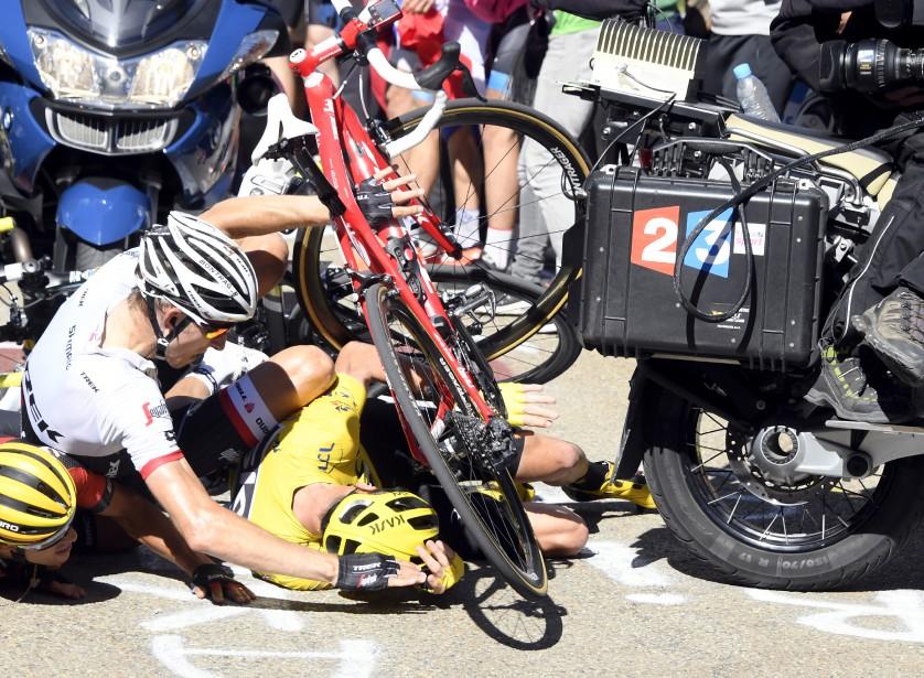 Peu avant le dernier kilomètre, Chris Froome chute après qu'une moto soit entrée en contact avec le cycliste Richie Porte. (AP, Bernard Papon)