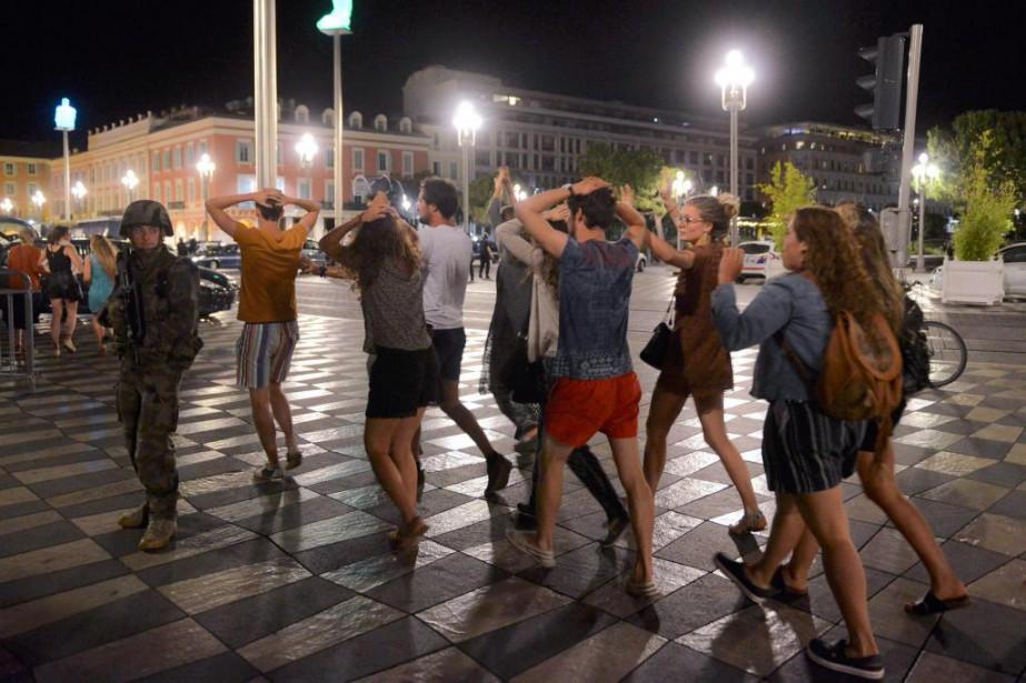 Des gens traversent une rue les mains en... (PHOTO JEAN-PIERRE AMET, REUTERS)