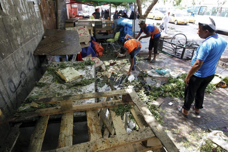 Des gens nettoyaient la scène.... (PHOTO SABAH ARAR, AGENCE FRANCE-PRESSE)