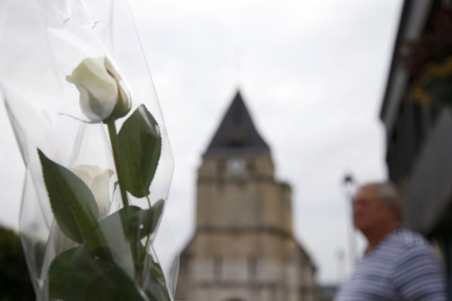 Roses blanches, ours en peluche et bougies s'accumulent... (PHOTO REUTERS)