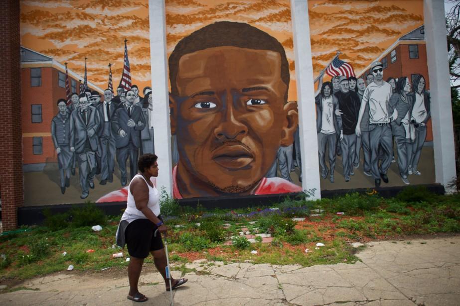 Une femme marche devant une murale à l'effigie... (Photo Mark MAKELA, archives AFP)