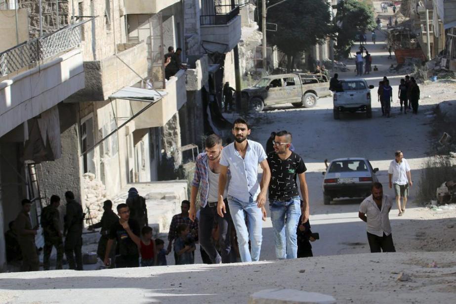 Des civils dans l'ancien quartier rebelle de Bani... (Photo GEORGE OURFALIAN, afp)