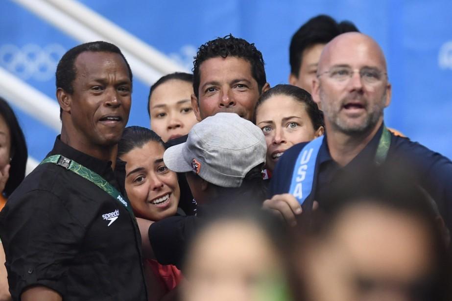 Meaghan Benfeito et Roseline Filion célèbrent avec leurs entraîneurs après avoir remporté la médaille de bronze. (Photo Frank Gunn, PC)