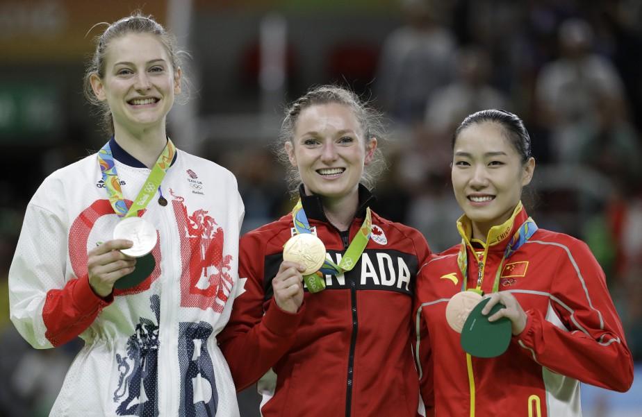 Rosie MacLennan (médaille d'or, au centre) sur le podium avec la Britannique Bryony Page (médaille d'argent, à gauche) et la Chinoise Li Dan (médaille de bronze, à droite). (Photo Julio Cortez, AP)