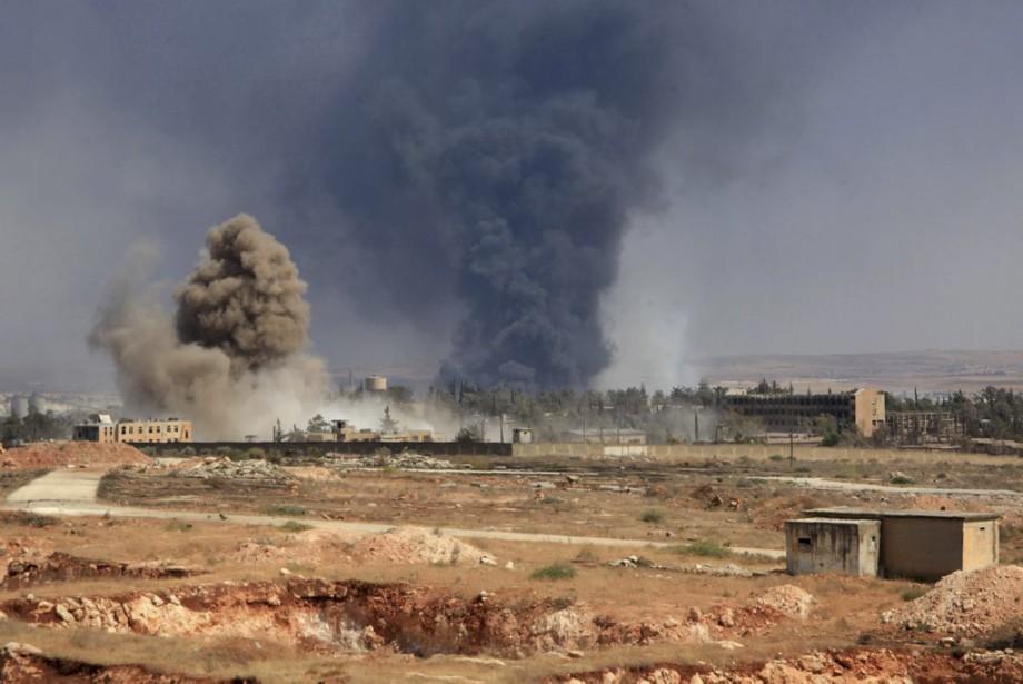 De la fumée s'élève au-dessus d'un quartier contrôlé... (PHOTO GEORGE OURFALIAN, AFP)