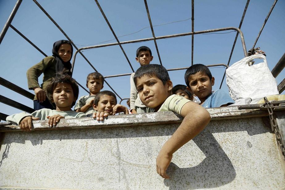 Des enfants syriens sont assis dans la boîte... (PHOTO DELIL SOULEIMAN, AFP)