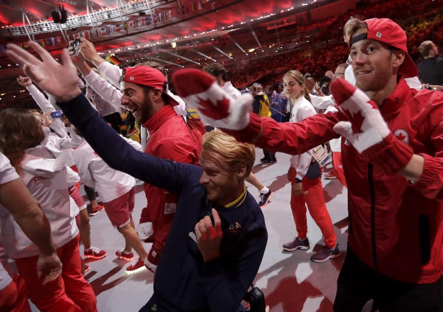 Des Canadiens posent fièrement lors du défilé des athlètes. (AP, David Goldman)