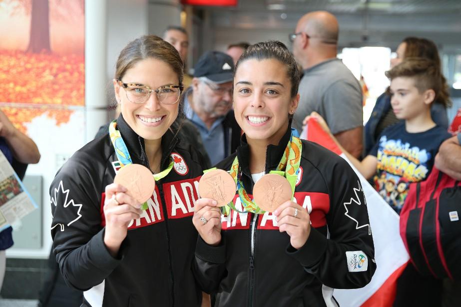 Les plongeuses Roseline Filion et Meaghan Benfeito montrent fièrement leurs médailles de bronze à leur arrivée à l'aéroport Montréal-Trudeau. (Photo Martin Chamberland, La Presse)