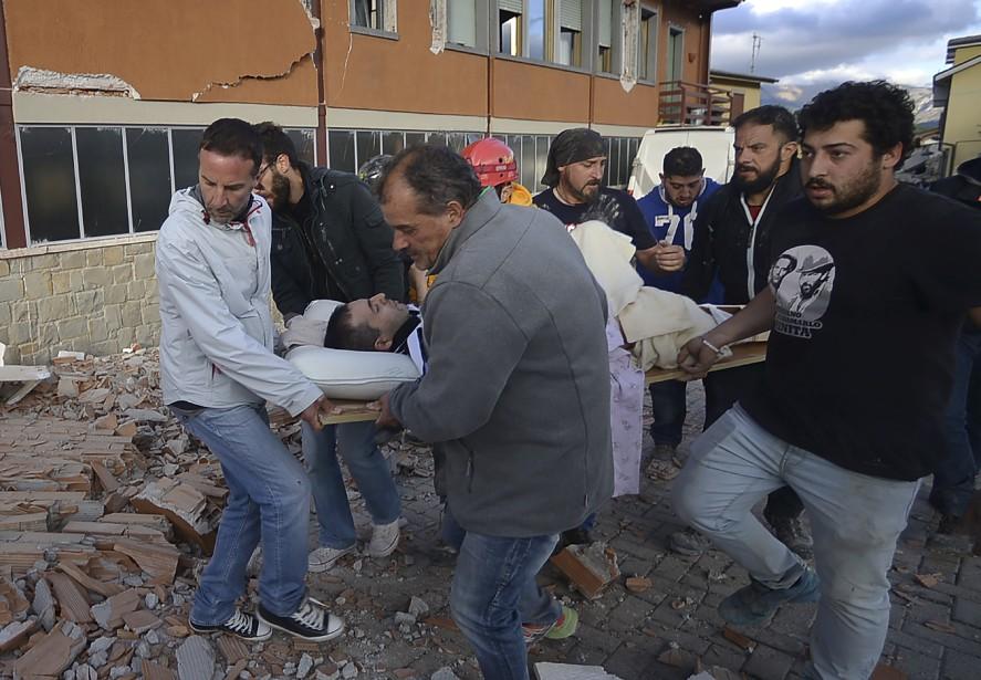 Des citoyens transportent un blessé hors des ruines d'un bâtiment à la suite du séisme qui a frappé la région d'Amatrice en Italie. (AFP, Filippo Monteforte)