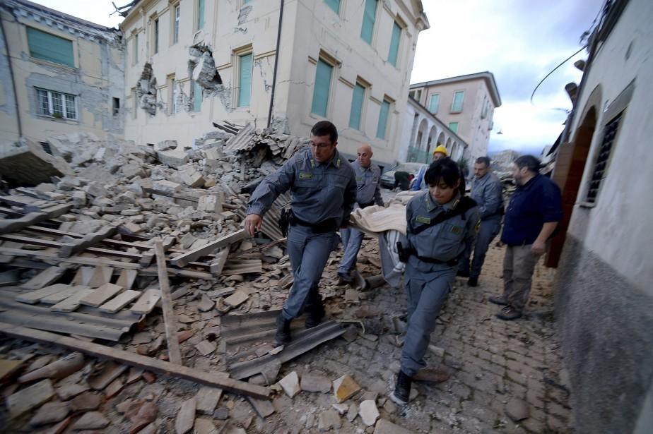 Des secouristes transportent un blessé hors des ruines d'un bâtiment à la suite du séisme qui a frappé la région d'Amatrice en Italie. (AFP, Filippo Monteforte)