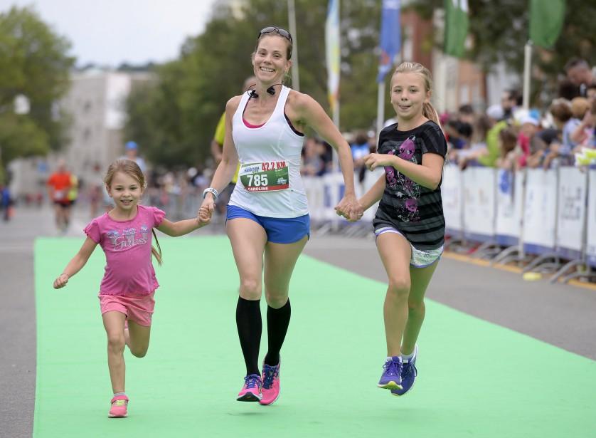 Cette marathonienne a eu droit à de la belle compagnie pour franchir le fil d'arrivée. (Le Soleil, Yan Doublet)