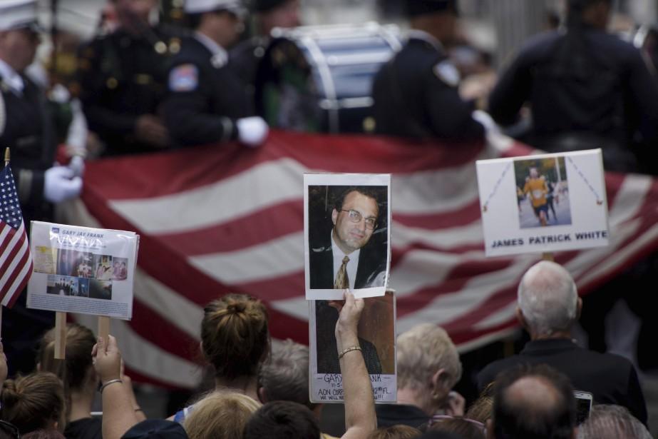 Des gens tiennent des photos des victimes des attaques au mémorial, à New York. (AFP)