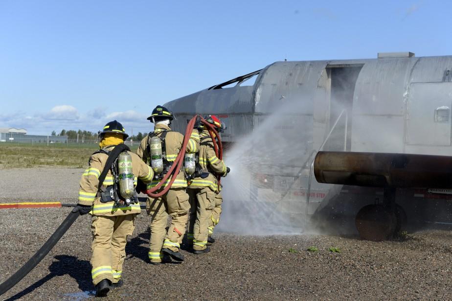 Les pompiers combattent ensuite les flammes au sol et se dirigent vers la batterie de l'appareil pour la désactiver. (Photo Le Progrès-Dimanche, Jeannot Lévesque)