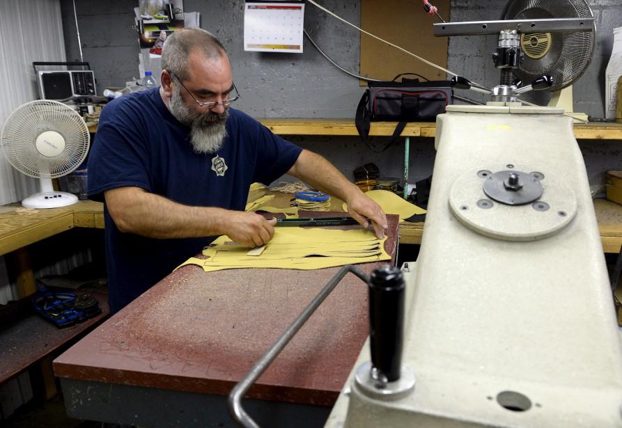 Steve Garneau coupe, à l'aide d'emporte-pièces et d'une presse, les morceaux de cuir qui serviront à fabriquer des mocassins. M. Garneau ne coupe qu'une épaisseur de cuir à la fois. (Le Soleil, Erick Labbé)
