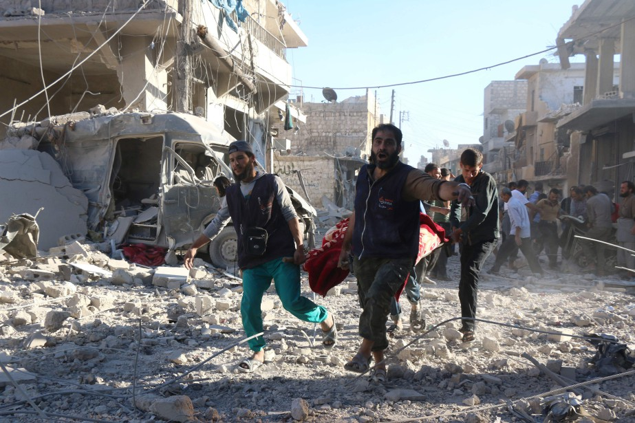 Des sauveteurs bénévoles transportent une personne blessée après... (PHOTO THAER MOHAMMED, AGENCE FRANCE-PRESSE)