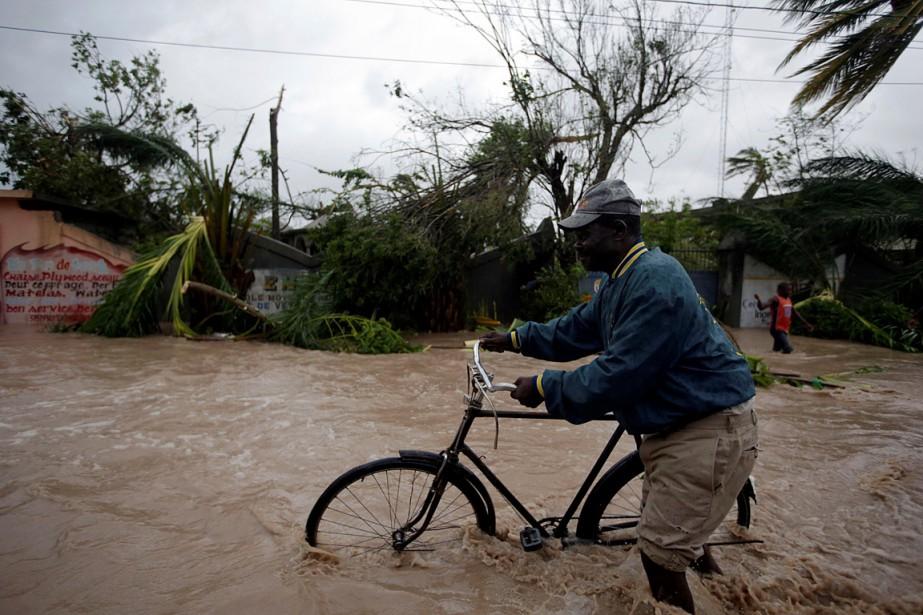 L'ouragan <em>Matthew</em> a violemment frappé Haïti. Les Cayes, troisième ville d'Haïti, a été «vraiment très endommagée», selon ledirecteur d'une ONG. Sur cette photo,un homme y pousse son vélo après le passage de Matthew. (Andres Martinez Casares, Reuters)