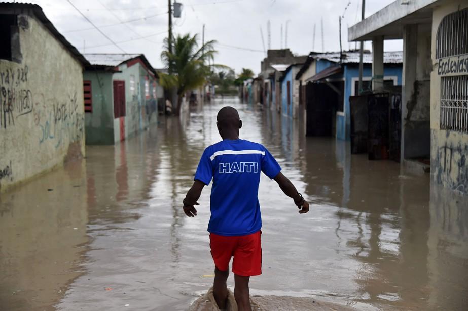 Un homme marche dans l'eau laissée par le passage de <em>Matthew</em> à Cité Soleil,une commune d'Haïti inondée, située dans l'arrondissement de Port-au-Prince. (HECTOR RETAMAL, AFP)