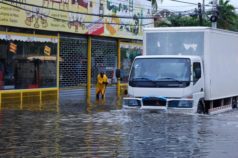 Le passage de l'ouragan sur la République dominicaine a tué quelques personnes et endommagé des centaines de bâtiments. Sur cette photo, un homme tente de dégager un égout à Santo Domingo. (Ezequiel Abiu Lopez, AP)