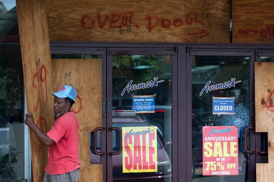 Un ouvrier a placardé les fenêtres de ce magasin à Kingston, la capitale de laJamaïque, avant le passage de <em>Matthew</em>. (Eduardo Verdugo, AP)