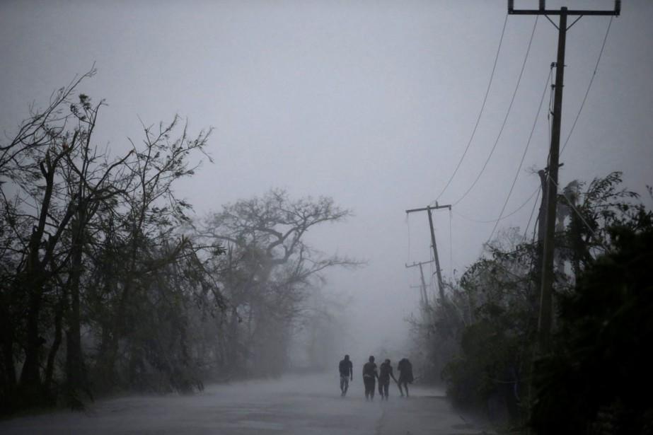 Des personnes bravent la pluie et les rafales à Les Cayes, en Haïti.Quelque 1800 maisons de cette ville ont été totalement inondées, selon un bilan partiel. (Andres Martinez Casares, REUTERS)