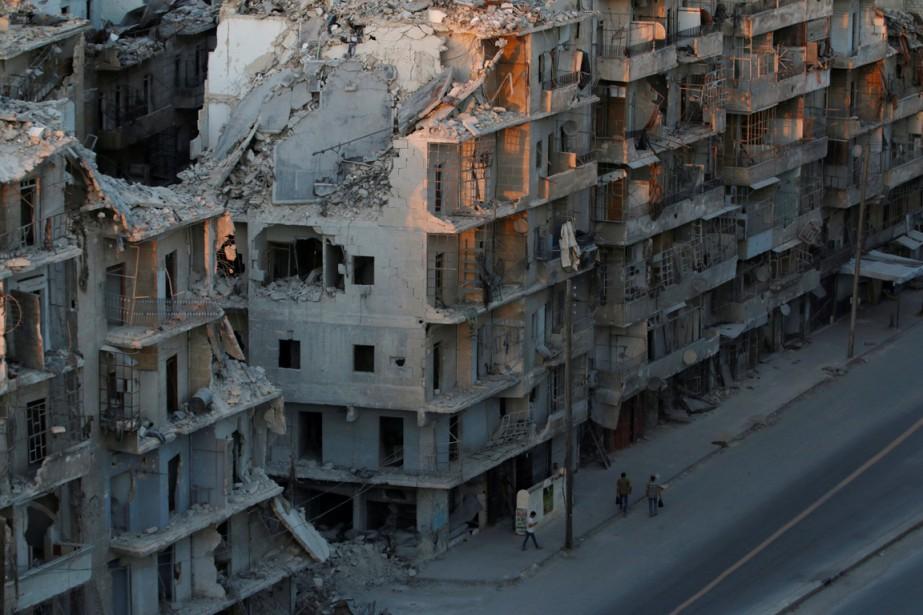 Des personnes marchent dans une rue défigurée du... (photo Abdalrhman Ismail, REUTERS)
