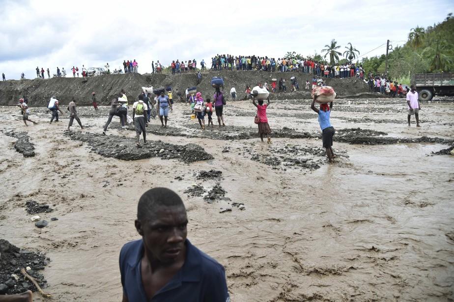 Des Haïtiens traversent la rivière La Digue à Petit Goave, où le pont s'est effondré. (AFP, HECTOR RETAMAL)