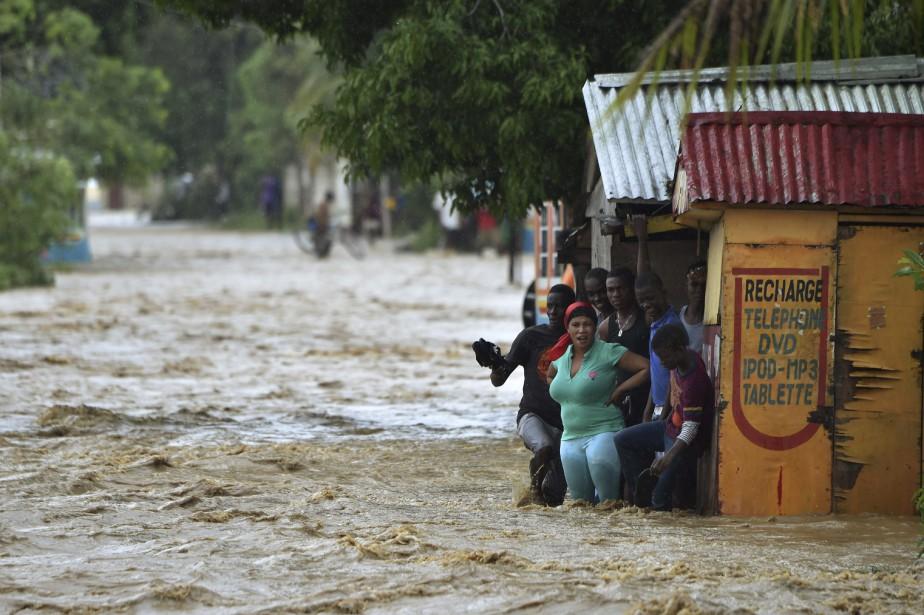 Des gens tentent de traverser la rivière La Rouyonne dans la commune de Leogane, au sud de Port-au-Prince. (AFP, HECTOR RETAMAL)