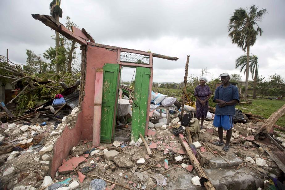 Saintanor Dutervil et sa femme se tiennent à côté de ce qui reste de leur maison dans la région des Cayes. (AP, Dieu Nalio Chery)