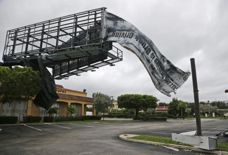 Une affiche installée sur un panneau publicitaire s'agite dans le vent après le passage de l'ouragan <em>Matthew</em>, le 7octobre à North Palm Beach, en Floride. (Photo Wilfredo Lee, AP)
