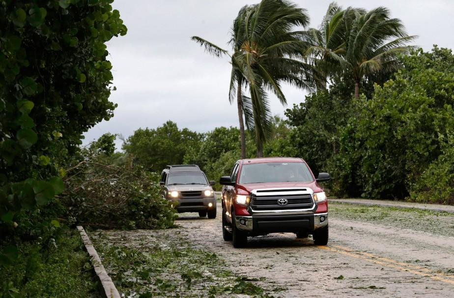 Des voitures évitent un arbre tombé sur une route de Jupiter, en Floride, le 7octobre. (Photo Wilfredo Lee, AP)